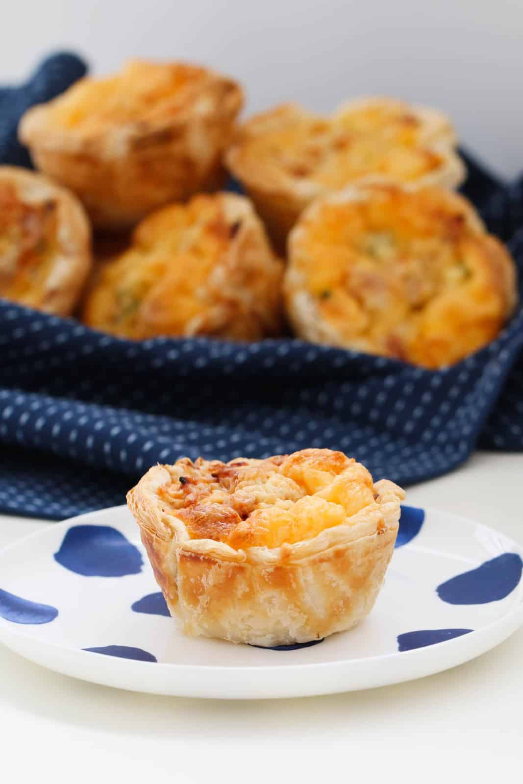 Blurred muffin sized puff pastry quiches on a crumpled blue tea towel behind an individual quiche on a white and blue plate
