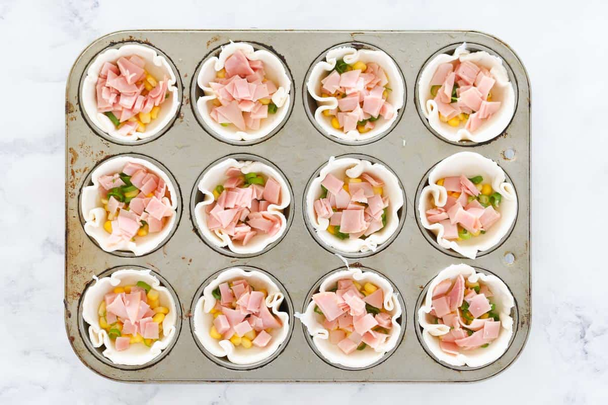 A 12-hole muffin tin, with raw puff pastry lining the holes, filled with chopped ham, corn kernels and spring onions