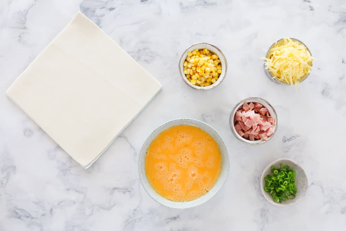 Sheets of puff pastry, and individual containers with egg, cheese, ham, corn and chives on a marble bench top.
