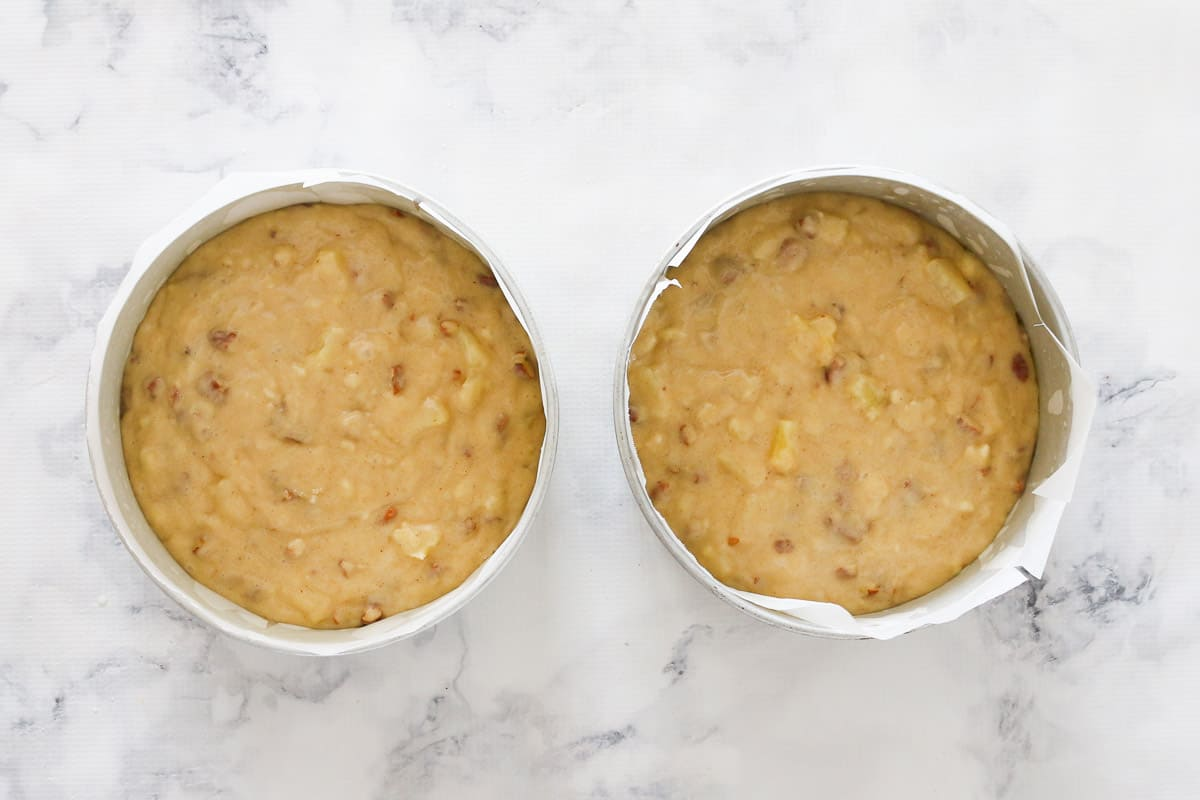 Two round cake tins filled with cake batter divided evenly between them