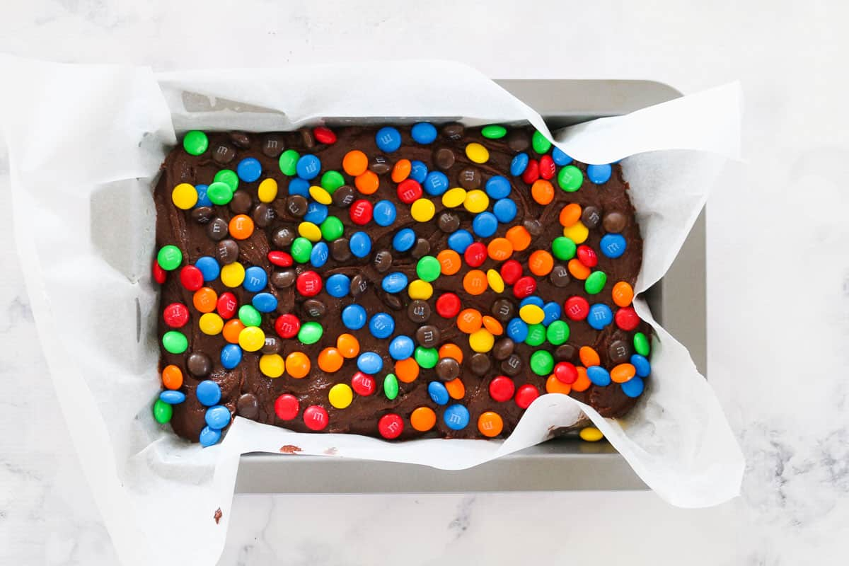 Top view of m&m chocolate brownies in pan, ready to be baked