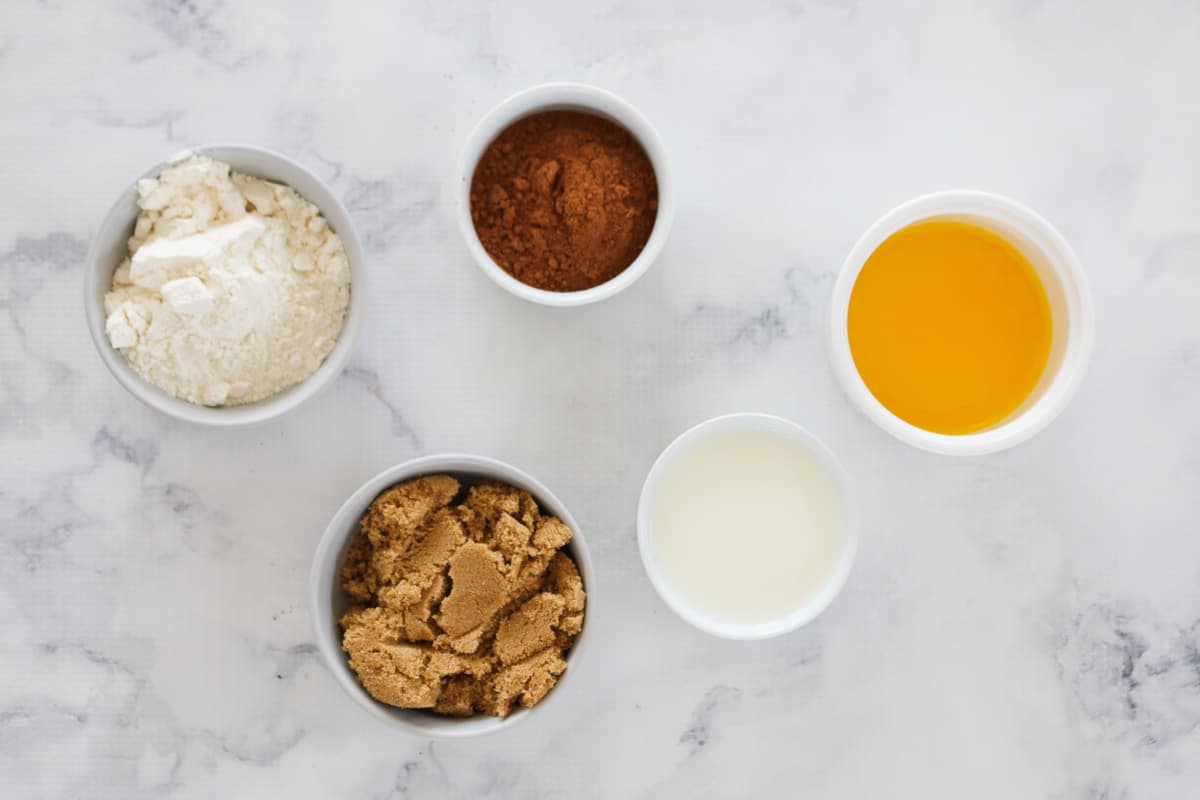 Cocoa powder, flour, brown sugar, milk, and melted butter - ingredients for microwave chocolate brownies in individual bowls