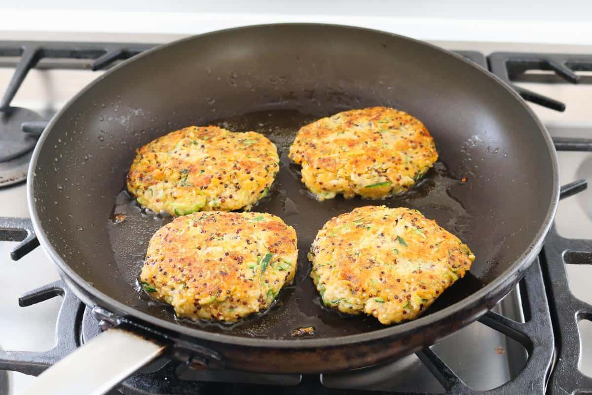 Four golden quinoa fritters in frying pan