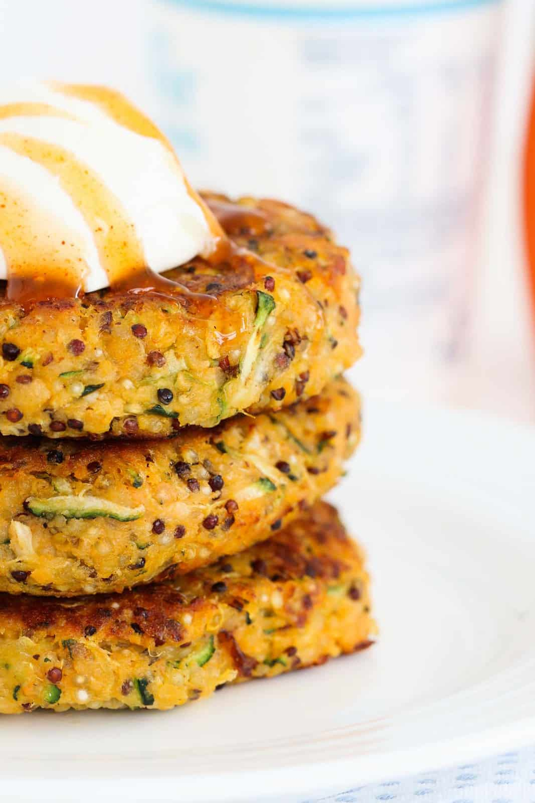 Three quinoa, zucchini and sweet potato fritters drizzled with sweet chilli sauce and sour cream.