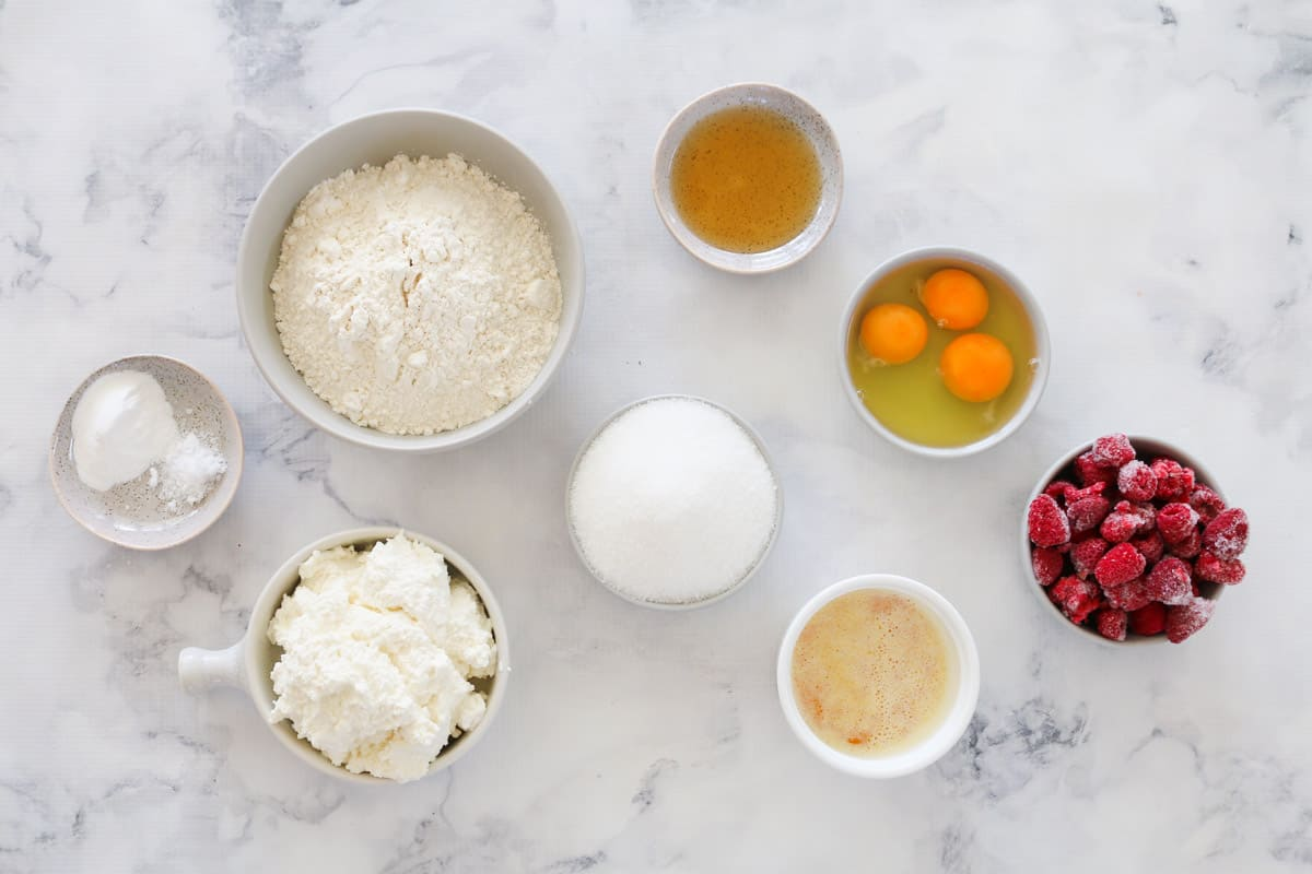 Top view of ingredients for raspberry ricotta cake in individual bowls.