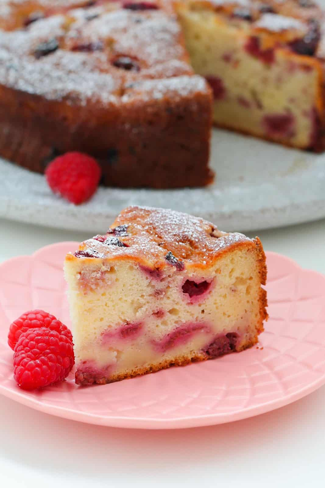 Close view of a serve of raspberry ricotta cake on pink plate with fresh raspberries