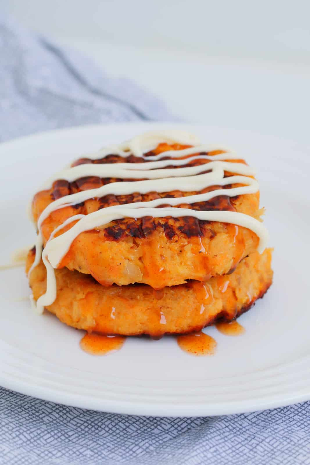 Two savoury tuna patties with sweet chilli sauce and kewpie mayonaise on top.