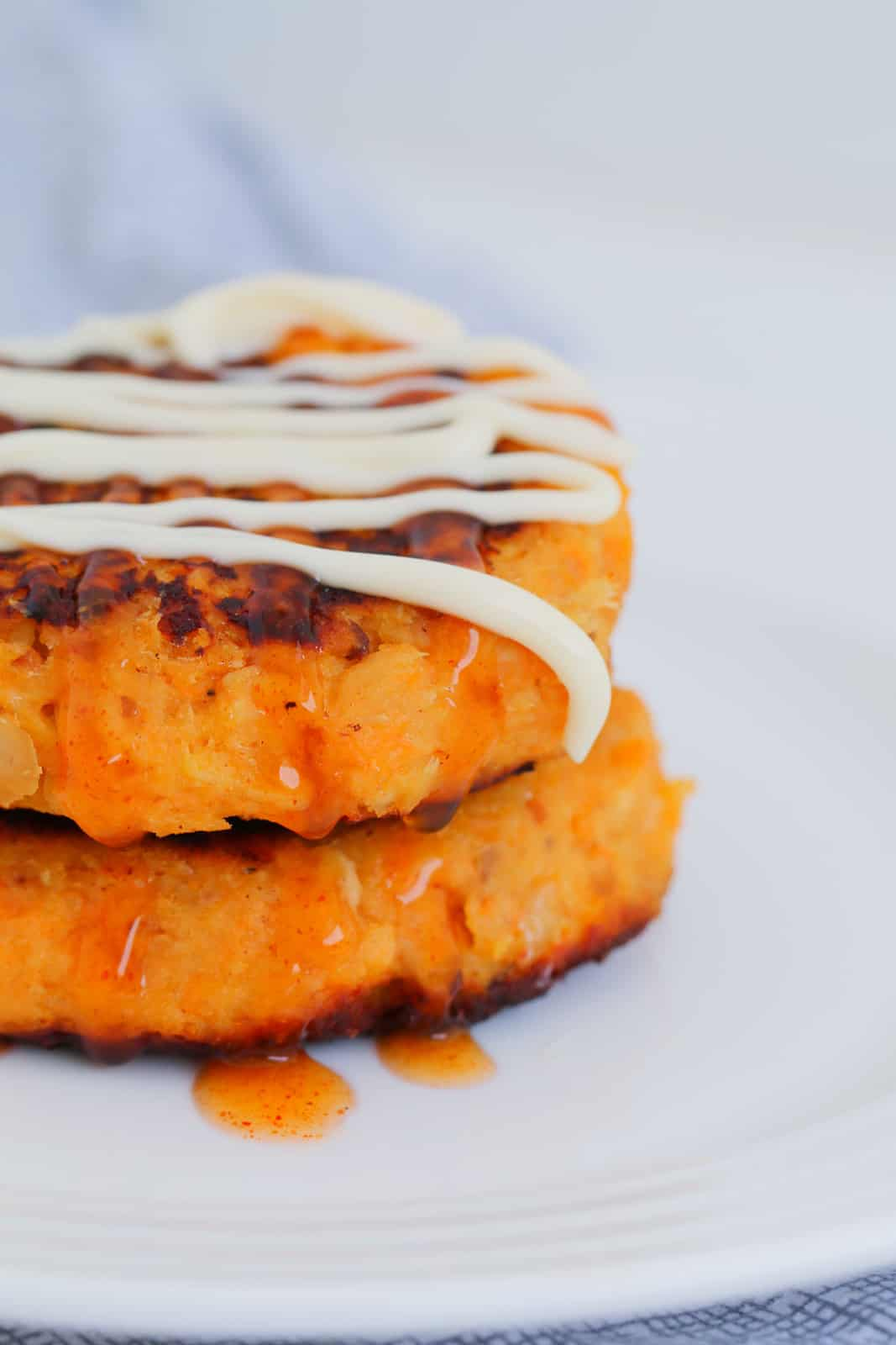 Two sweet potato and tuna patties, drizzled with sweet chilli sauce and Kewpie mayonnaise.