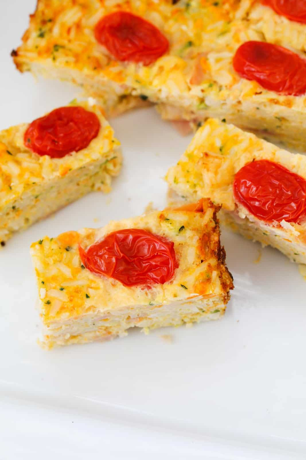 An overhead shot of cherry tomatoes on top of a golden vegetable bake.