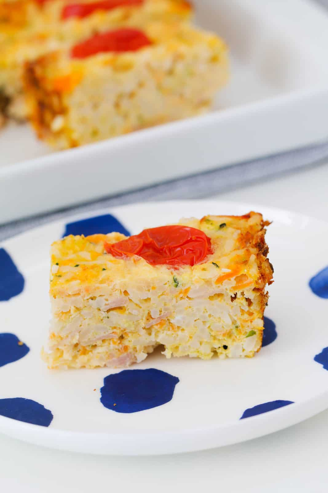 A piece of vegetable slice with zucchini, carrot, ham and rice on a blue and white plate.