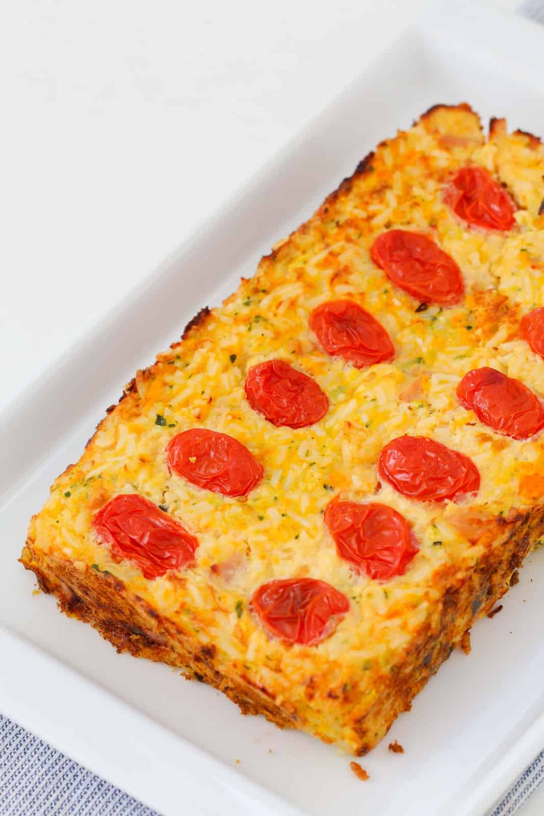 A vegetable and rice loaf with cherry tomatoes on top, served on a white plate.