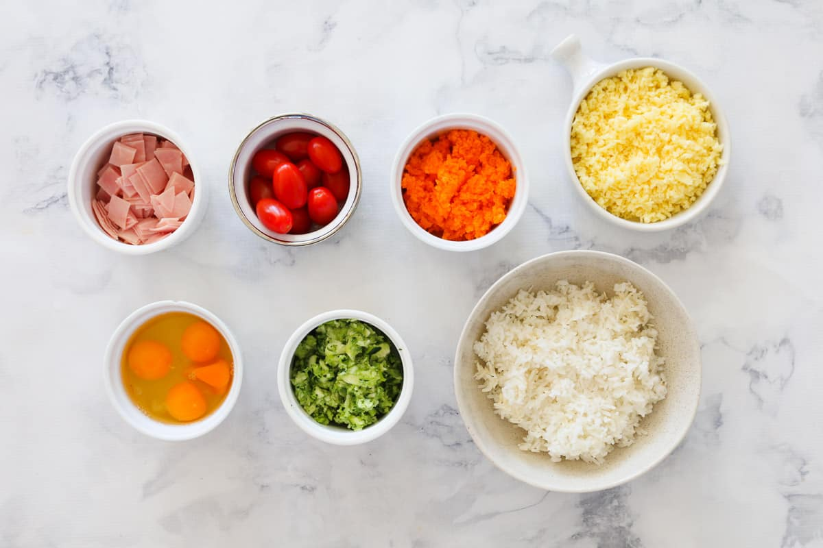 The ingredients for a vegetable slice made with rice, grated vegetables, eggs, cheese and ham.