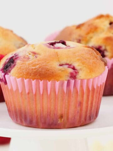 A muffin with red berries in a pink paper case on a white cake stand.