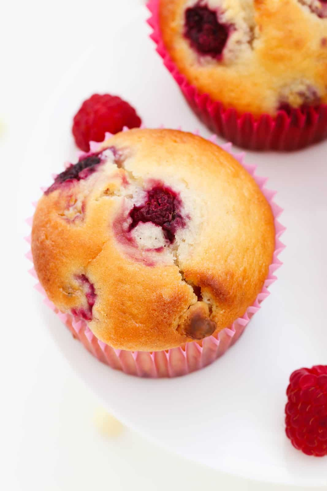 An overhead view of muffins with raspberries, in paper cases on a white cake stand.
