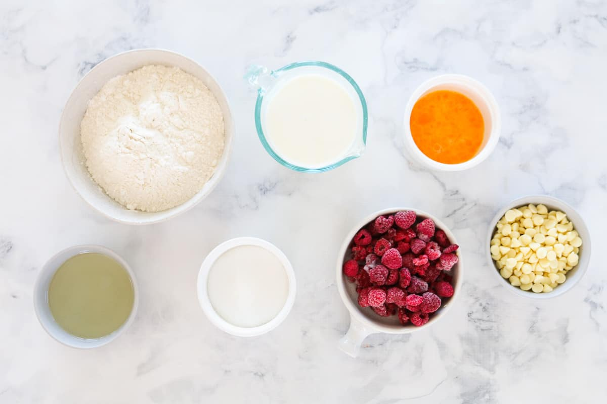 Ingredients to make raspberry and white chocolate muffins measured into small individual bowls.