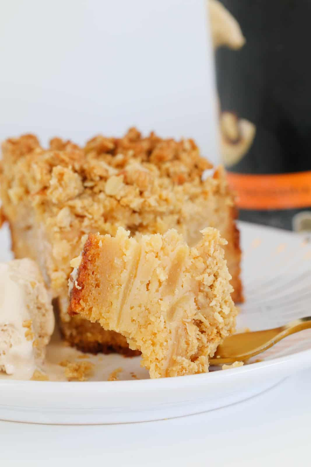 A serve of Apple Crumble Cake with some on a fork showing layers of sliced apple