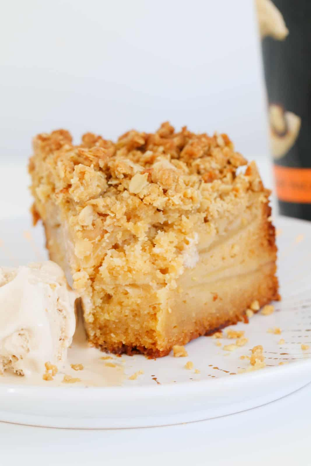 A serve of cake with a thick layer of crumble on top, and filled with layers of sliced apple.