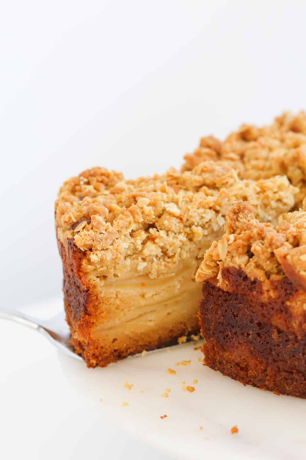 A serve of apple crumble cake being removed from the rest of the cake, showing layers of apple inside