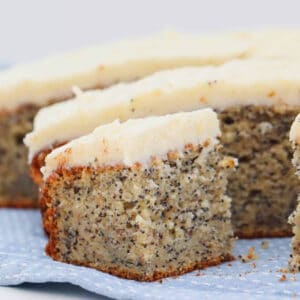 A piece of frosted poppy seed cake on a blue and white tea towel in front of the rest of the sliced cake.