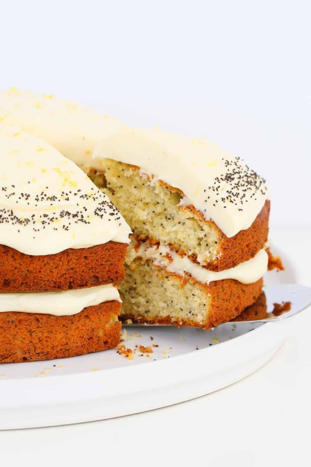 A slice of poppy seed cake with cream cheese frosting being removed from the rest of the cake.