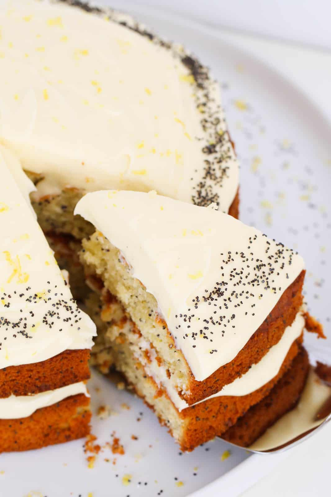 A slice of cream cheese frosted lemon and poppy seed cake being removed with a cake slice.