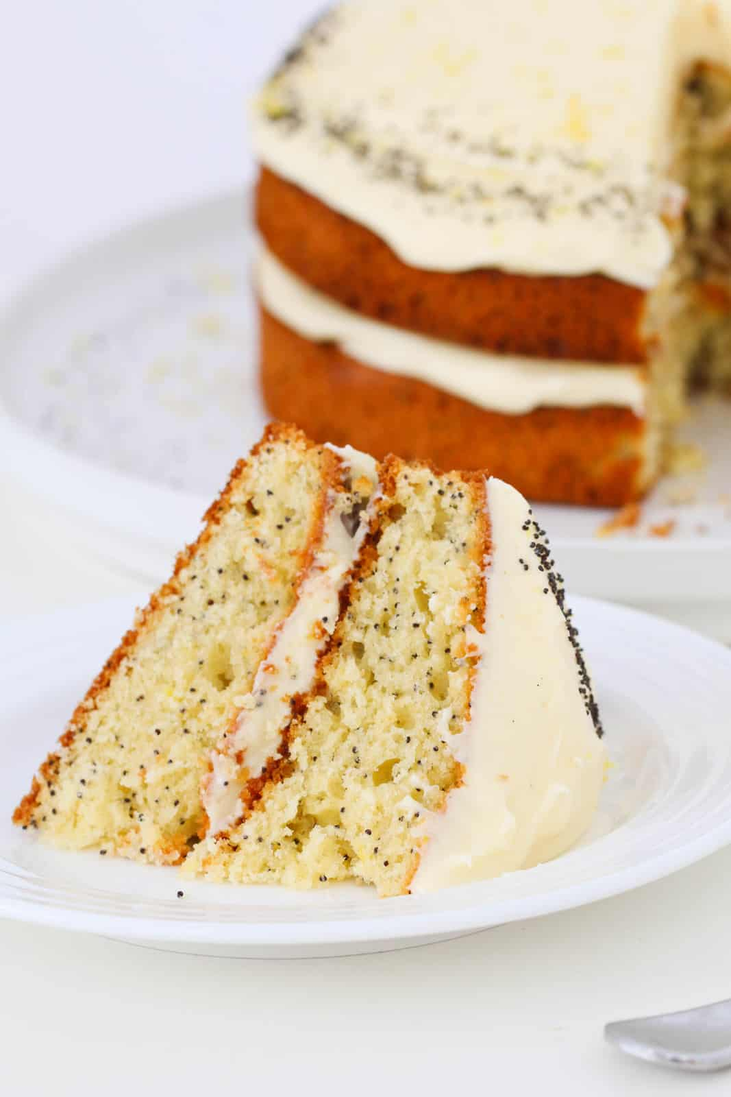 A slice of double layered lemon cake with poppy seeds and cream cheese frosting.