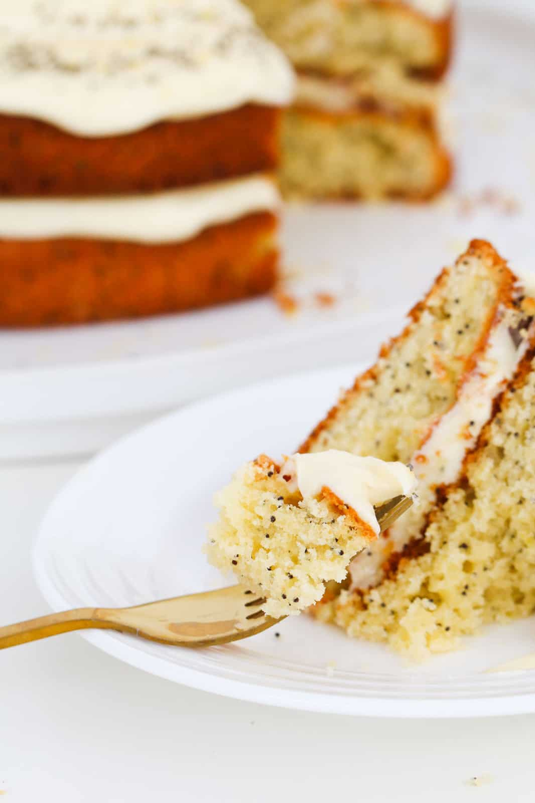 A fork with lemon and poppy seed cake with cream cheese frosting on a plate.