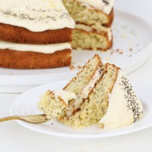 A fork with poppy seed cake with cream cheese frosting on a plate.