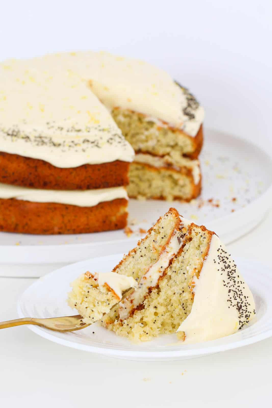 A fork filled with lemon poppy seed cake on a plate, in front of the rest of the cake