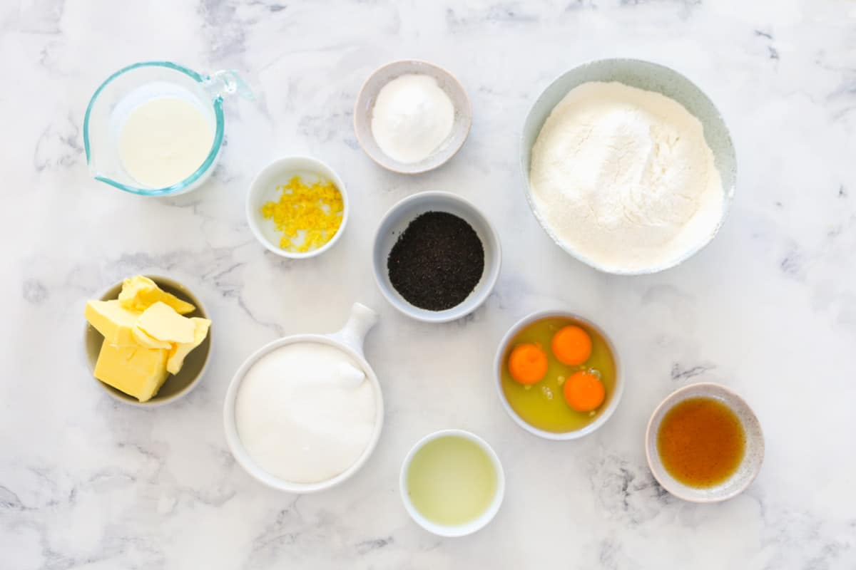 The ingredients for lemon poppy seed cake in individual bowls.