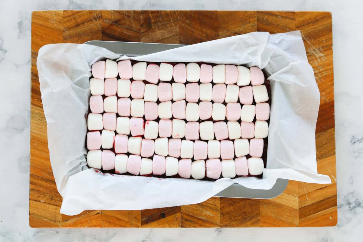 Marshmallow slice base with pink and white marshmallows cut and placed on top of jam layer in baking tin.