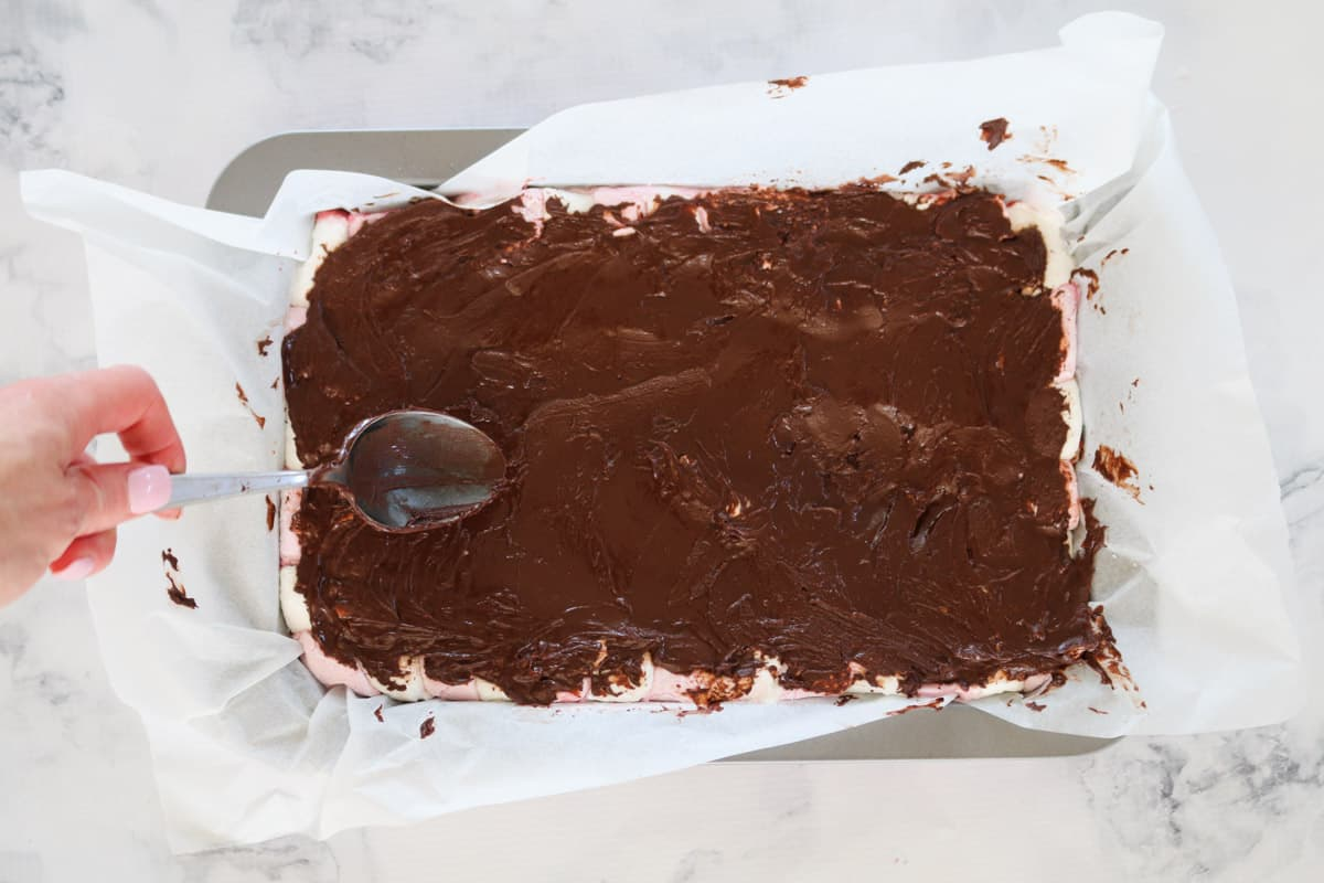 A slice tin of marshmallow slice with chocolate being spread on top with a spoon