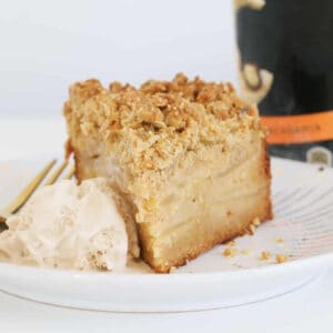 A slice of apple crumble cake with a scoop of ice-cream on the side.