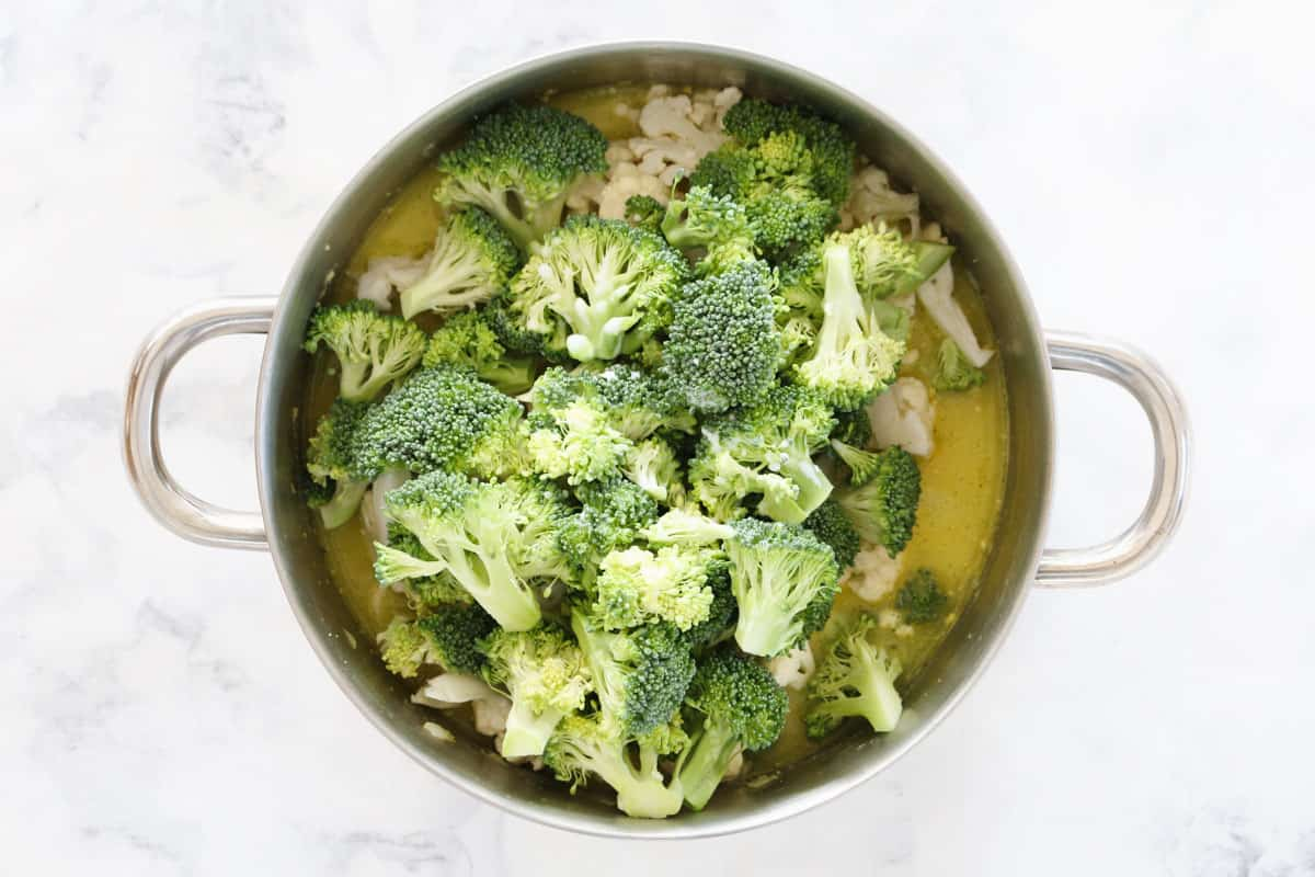Broccoli and cauliflower florets added to a liquid in a stainless steel double handled saucepan