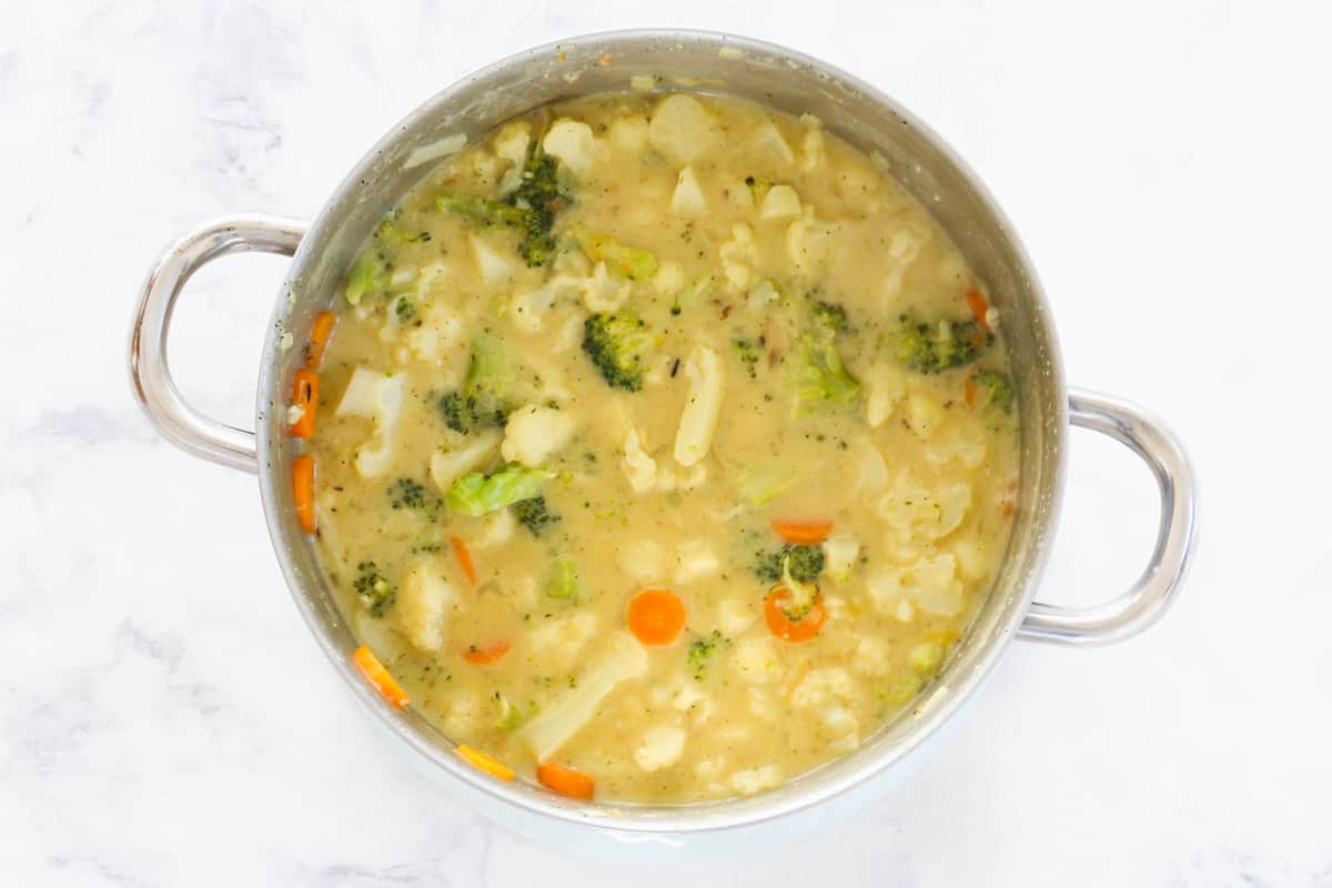 A pot with mixed vegetables and milky stock liquid in a saucepan