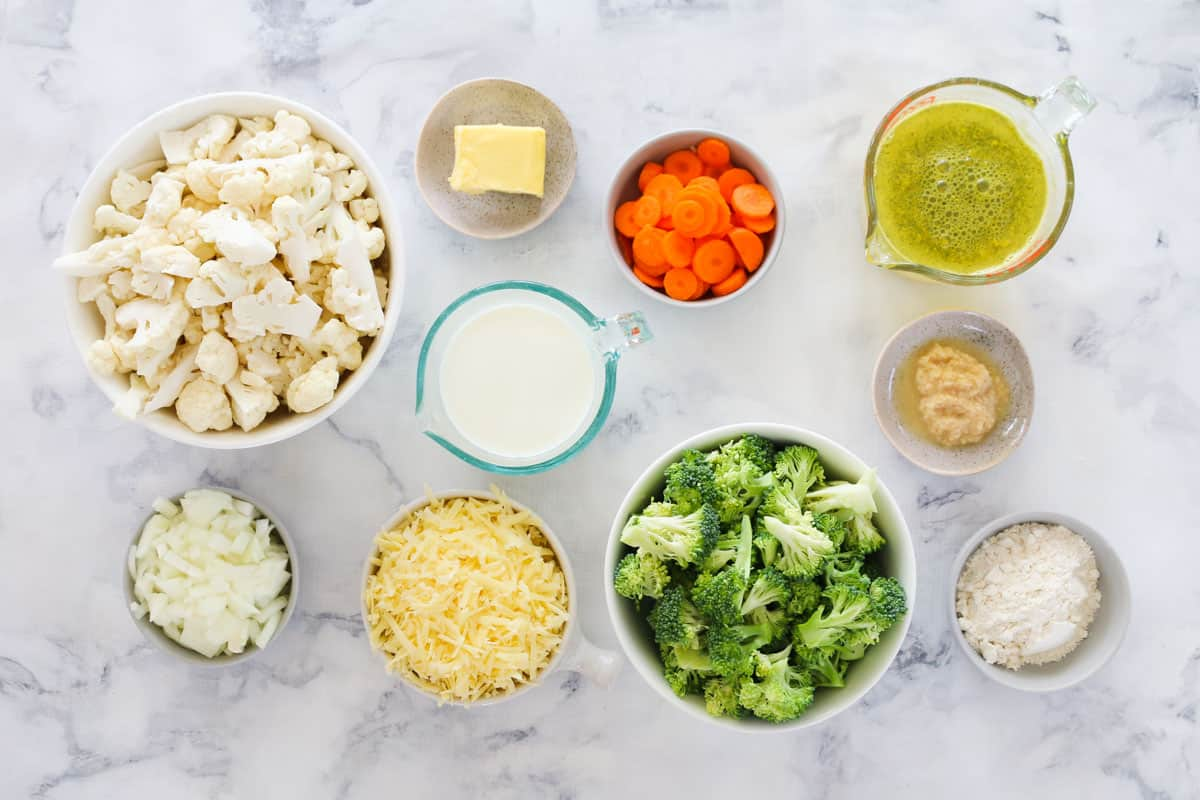 Individual containers with broccoli and cauliflower soup ingredients measured out on a marble bench top
