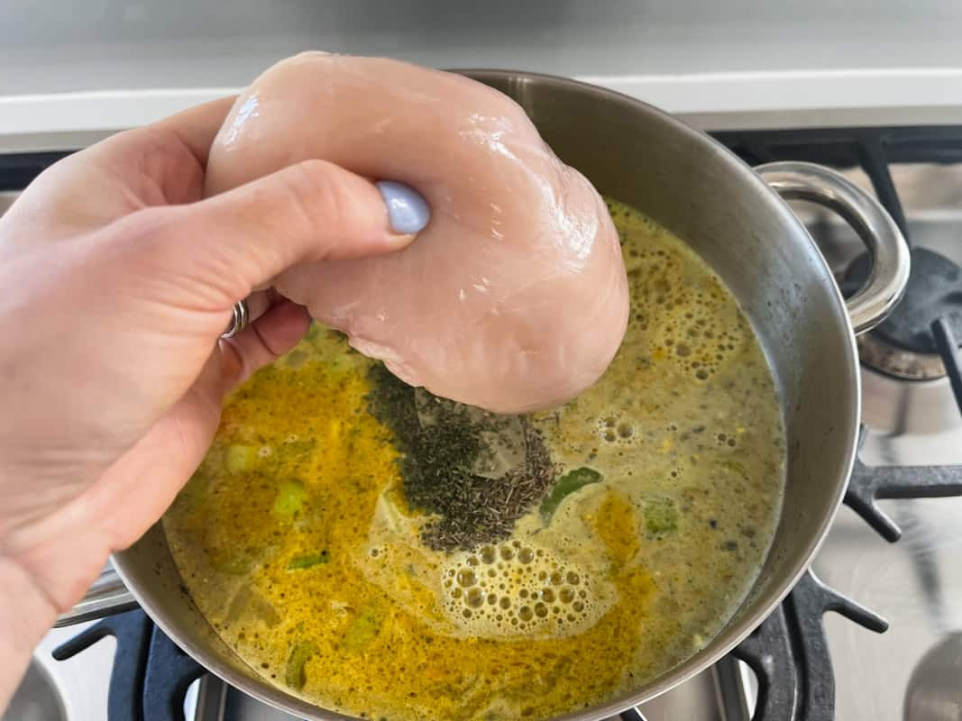 A whole raw chicken breast being added to a pot with stock and vegetables.