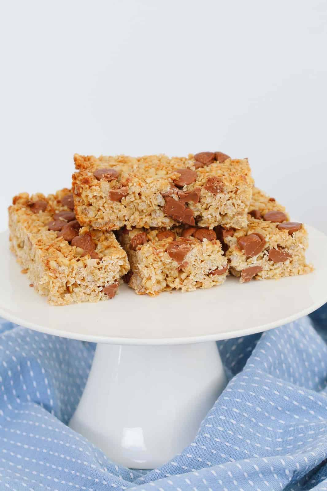 Granola bars made with chocolate chips, stacked on a white cake stand with a blue teatowel around the base
