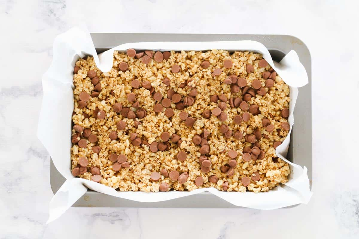 Granola mixture pressed into a baking paper lined rectangular baking tin