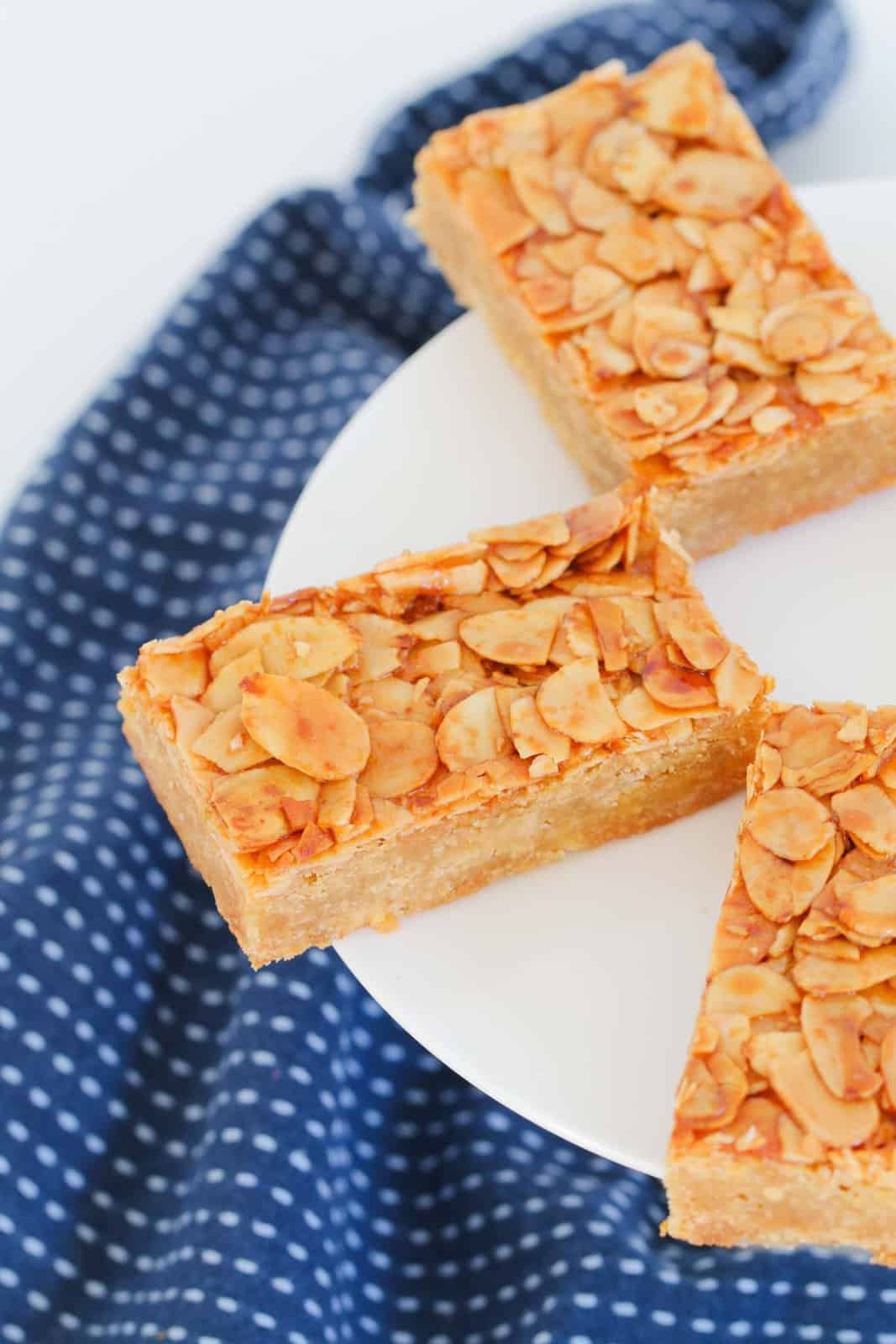 pieces of a slice with a biscuit base topped with flaked almonds on a white plate