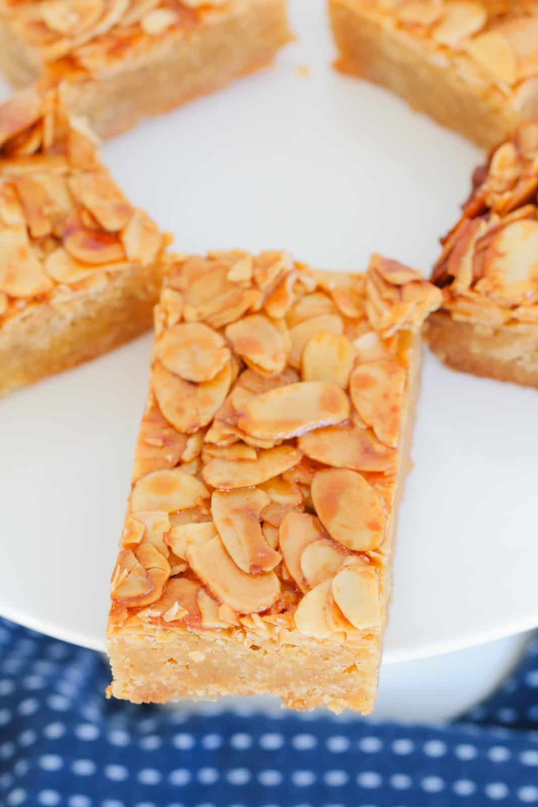 A close up view of pieces of honey almond slice on a white plate