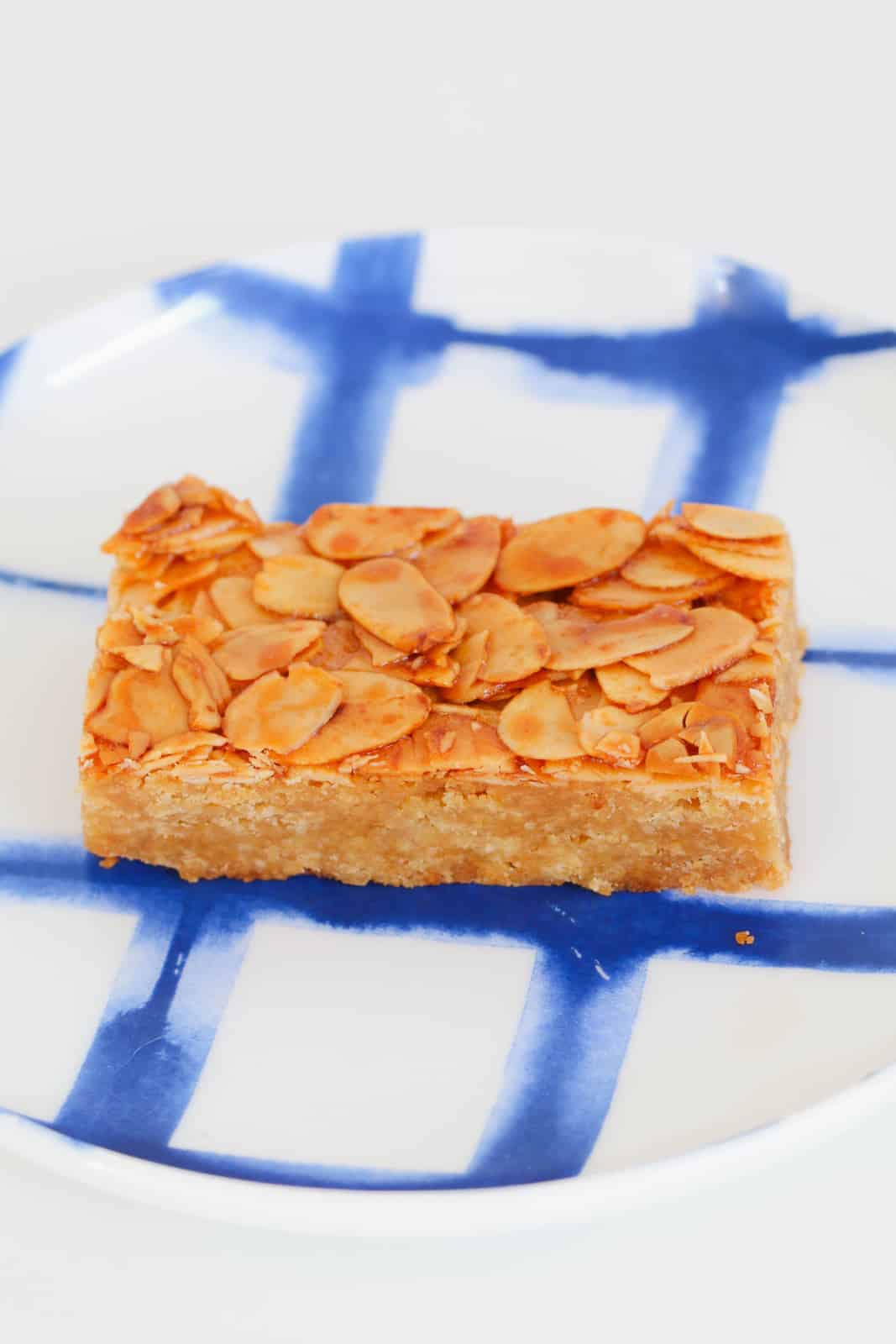 A piece of almond slice on a blue and white plate