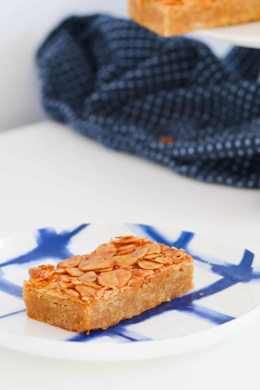 A piece of slice with flaked almonds on top, served on a blue and white plate
