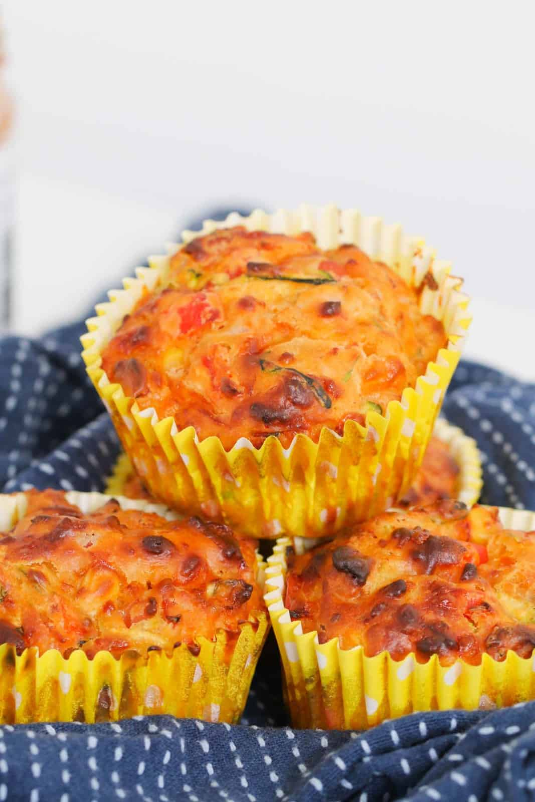 A stack of vegetable savoury muffins in yellow paper muffin cases.