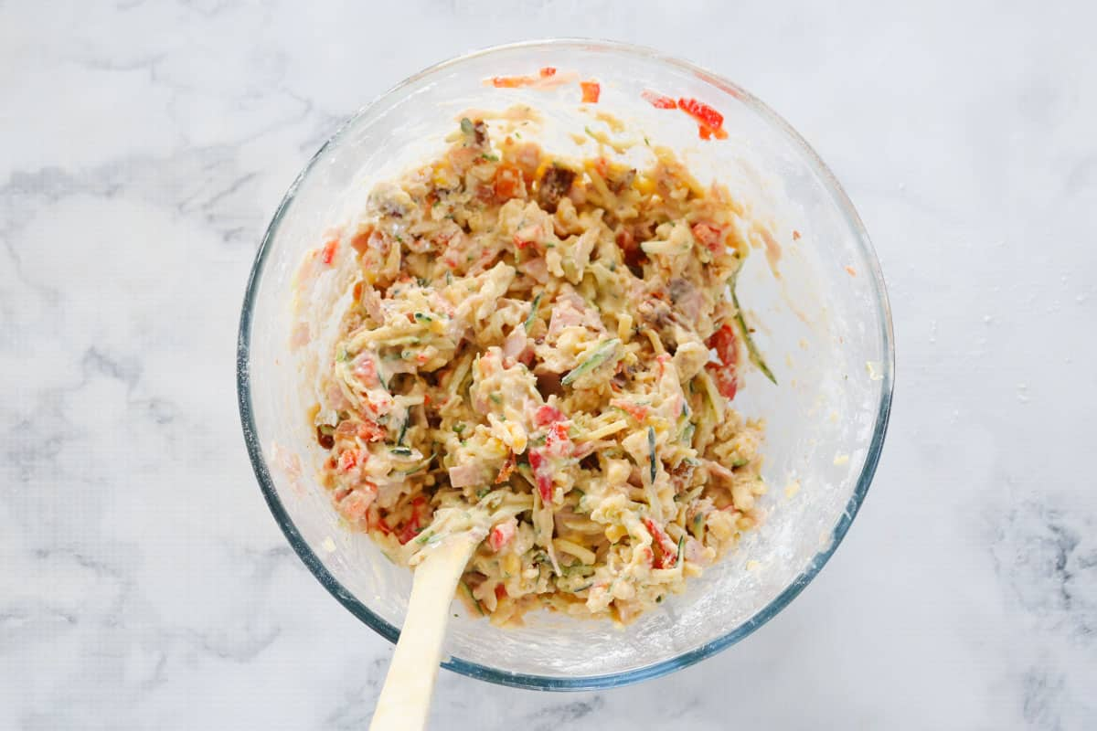 The chopped vegetables, ham and wet ingredients mixed together with the flour in a bowl.