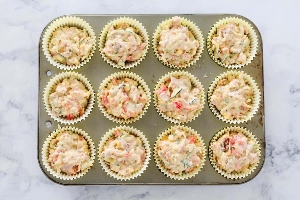 Muffin cases with uncooked vegetable savoury muffin mixture in them, in a muffin tray ready to be baked.