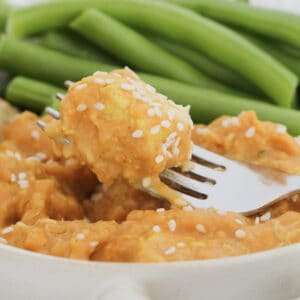 A piece of butter chicken on a fork with green vegetables.