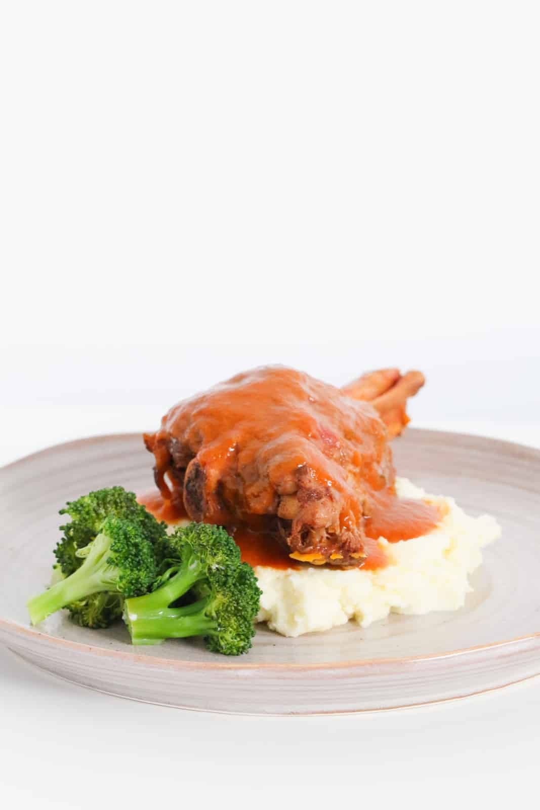 A lamb shank covered in a rich tomato gravy arranged on a bed of mash with broccoli florets.