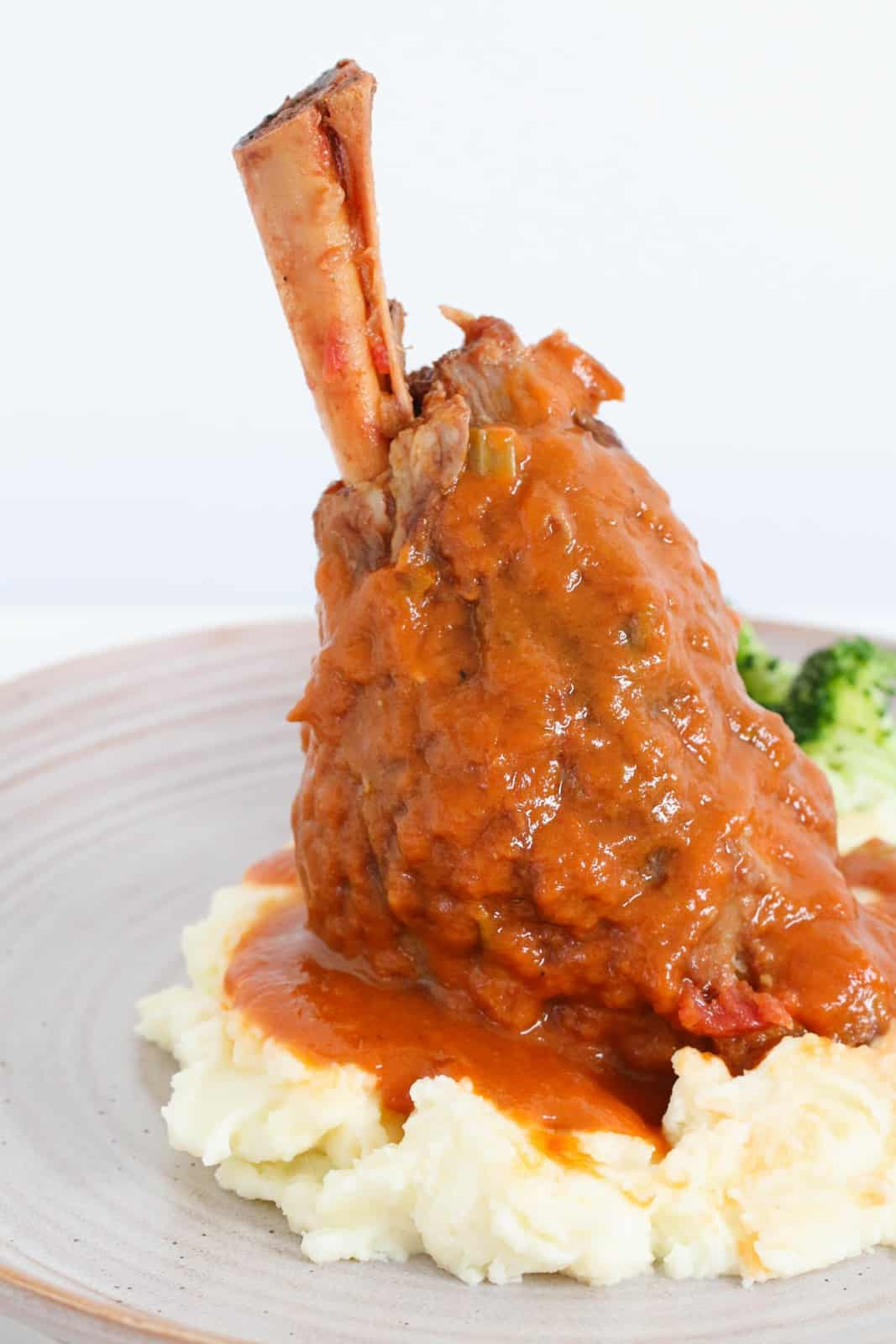 A lamb shank covered in a rich gravy and served on a bed of mash with broccoli.
