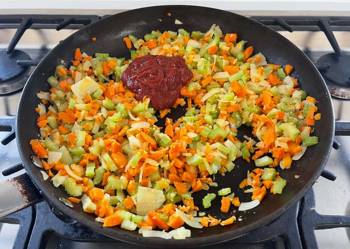 A non stick frying pan on a stove top with sautéed diced vegetables and a dollop of tomato paste added.